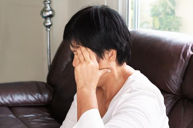 Старая женщина, страдающая от головной боли, стресса, мигрени, концепции проблемы со здоровьем