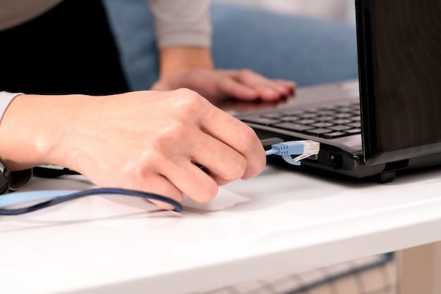 女性の手はラップトップケーブルにラップトップポートを差し込んでいます