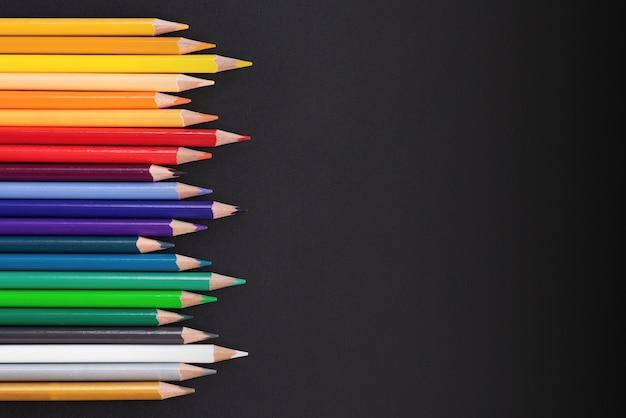チームワークのコンセプト。コピースペースと黒の背景に色鉛筆のグループ