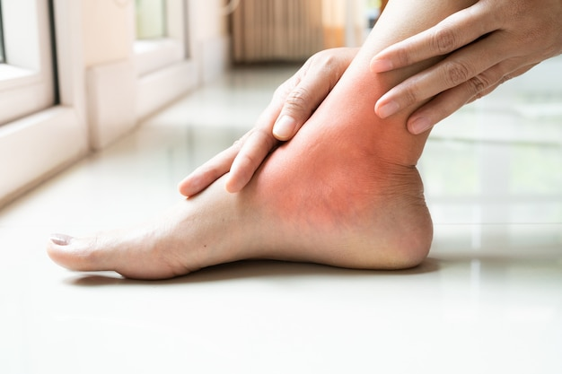 女性の足首の怪我/痛い、女性の痛みの足首の足に触れる