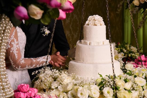 花嫁と手の手がウェディングケーキを切る。