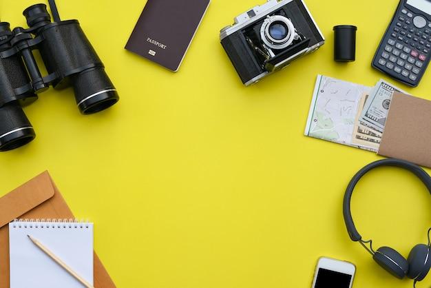 写真家の黄色の机の背景上のアクセサリー