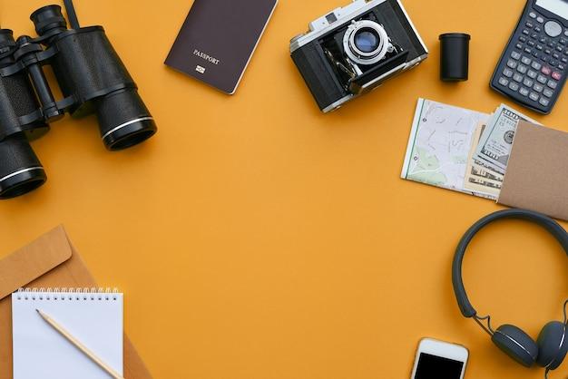 写真家のオレンジ色の机の背景上のアクセサリー