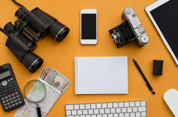オレンジ色の机の背景にアクセサリーのフラットレイアウト