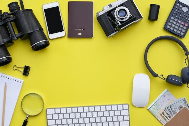 黄色の机の背景にアクセサリーのフラットレイアウト