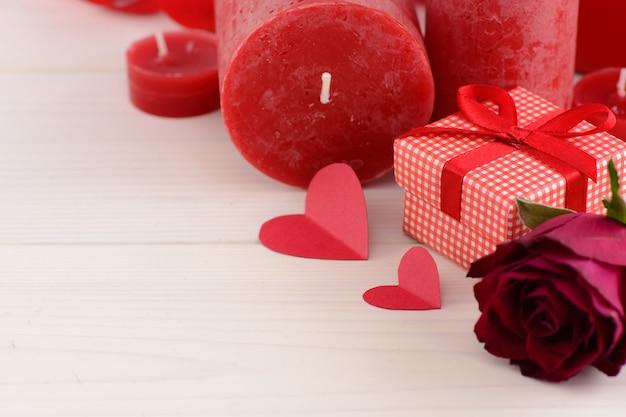 白い木製のテーブルの上の赤いバラとバレンタインデー赤背景。