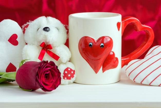 マグカップ、バラとテディベアとバレンタインの日の赤い背景。
