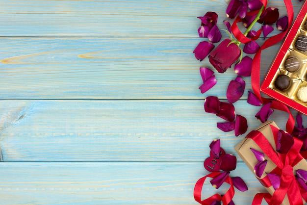 バラと青い木製のテーブルの上のチョコレートのバレンタインの日ロマンチックな装飾。