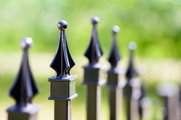 黒い装飾的な金属の塀、角のある鉄の棒および曲げられた上部。