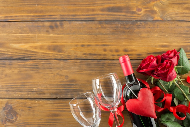 バラとワインと茶色の木製のテーブルの上のバレンタインデーのロマンチックな装飾