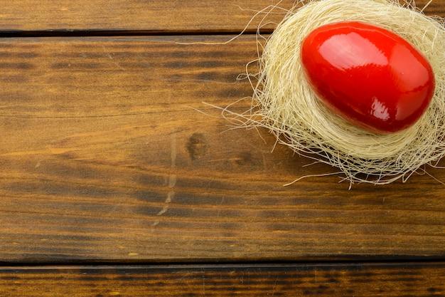 茶色の木製のテーブルの上の巣に赤のイースターエッグ。上面図、スペースをコピーします。