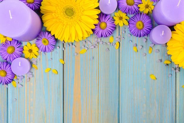 黄色のガーベラ、紫の庭の花、青い木製のテーブルの上のろうそく。