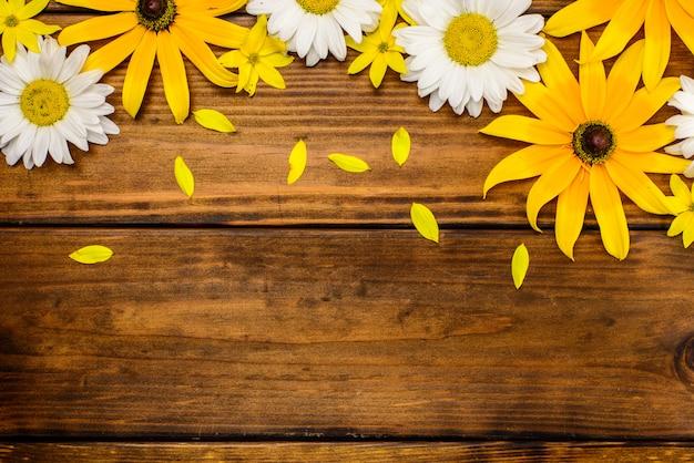 白いヒナギクと茶色の木製のテーブルの上の庭の花