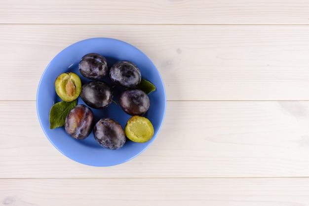 Тарелка вкусной спелой сливы на белом деревянном столе