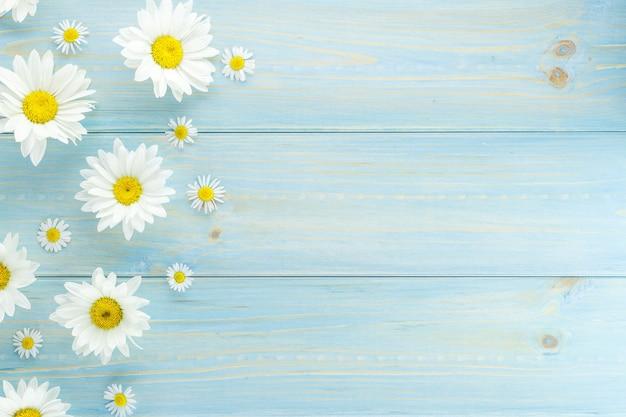 薄い青色の服を着た木製のテーブルに、白いデイジーと庭の花。