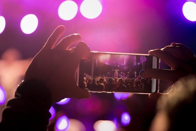 音楽祭では、男性がスマートフォンでコンサートを録音します。