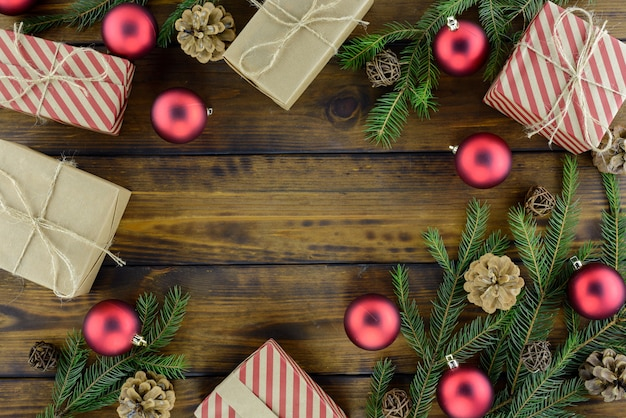 クリスマスの飾り、ギフト用の箱、松ぼっくり、茶色の木製のテーブルに赤いボール