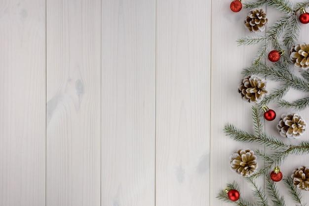 クリスマスの飾り、松ぼっくり、白い木製のテーブルの赤いボール。平面図、コピースペース。