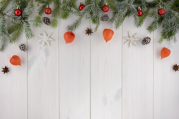 クリスマスの飾り、松ぼっくり、星、白い木製のテーブルの上の赤いボール。平面図、コピースペース。