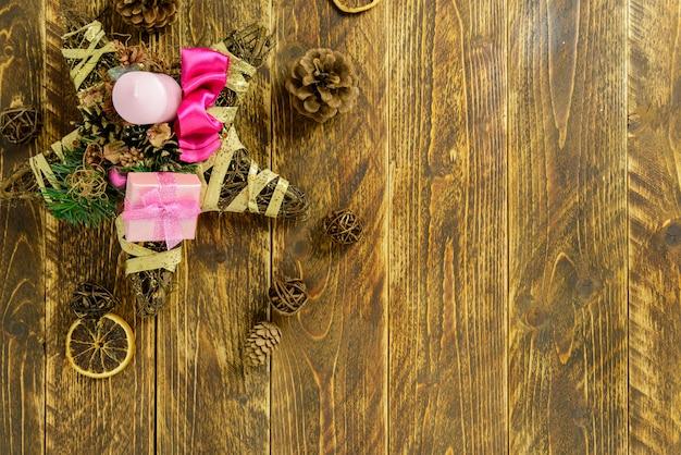 クリスマスの装飾、ピンクのキャンドル、茶色の木製テーブルの上の松ぼっくり。トップビュー、コピースペース。