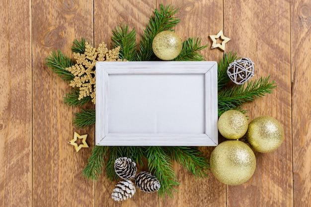 黄金色のボールと茶色の木製テーブルの上の雪のクリスマスの装飾の間にフォトフレーム。トップビュー、スペースをコピーするフレーム