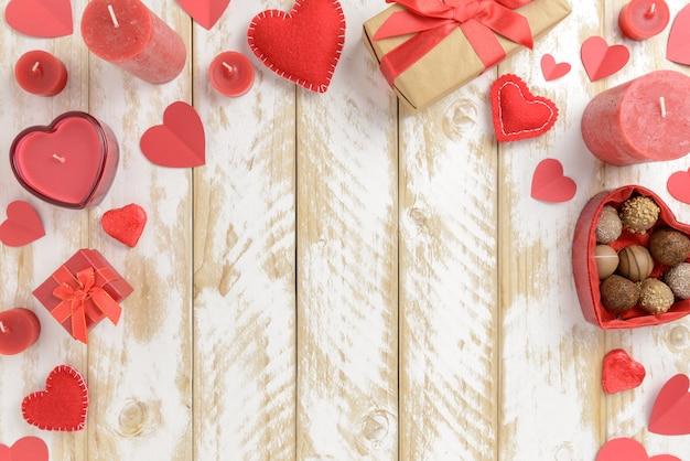 心と白い木製のテーブルの上のキャンドルでバレンタインの日ロマンチックな装飾。トップビュー、コピースペース。