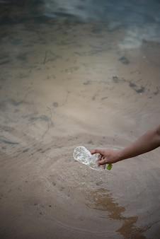 Рука забрать пластиковую бутылку из воды