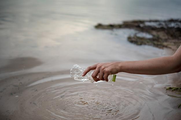 手は水からペットボトルを拾う