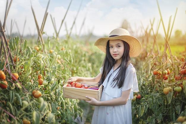 Азиатская милая маленькая девочка с красными помидорами