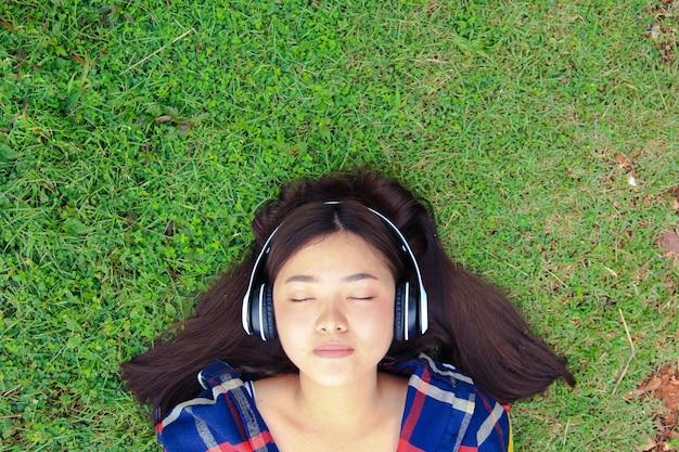 ヘッドフォンを着ている若い美しい女性のクローズアップの肖像画