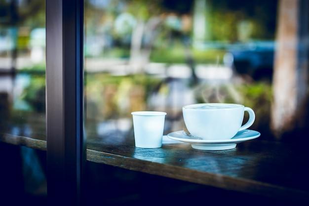 カフェのテーブルのホットコーヒーカップ