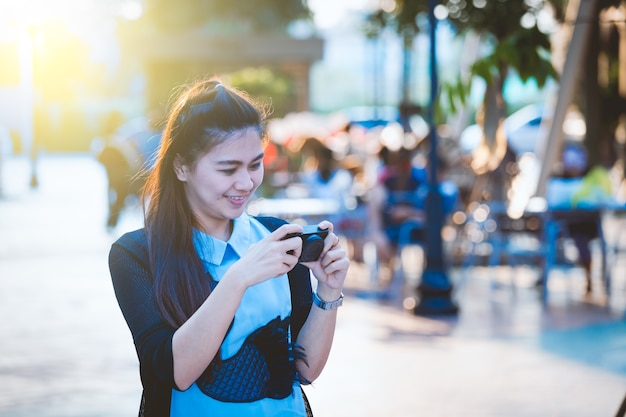 自由な日にカメラ付きアジアの女性は街でリラックスしています