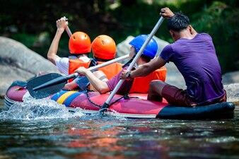Группа людей рафтинга в реке с гидом