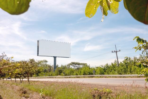 Пустой придорожный рекламный щит на яркий солнечный день голубого неба с областью для вашего сообщения