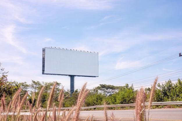 Придорожный рекламный щит на яркий солнечный синий день неба с областью для вашего сообщения
