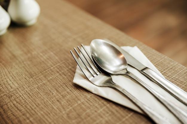フォーク、スプーン、ナイフ、白い紙、古い木製のテーブル、朝食用。