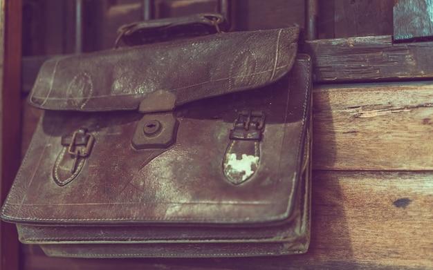 Старые школьные кожаные сумки, висящие на деревянной стене
