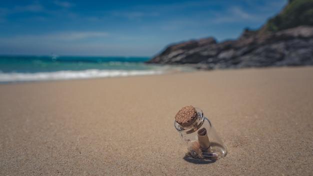 砂のビーチで瓶の中のメッセージ