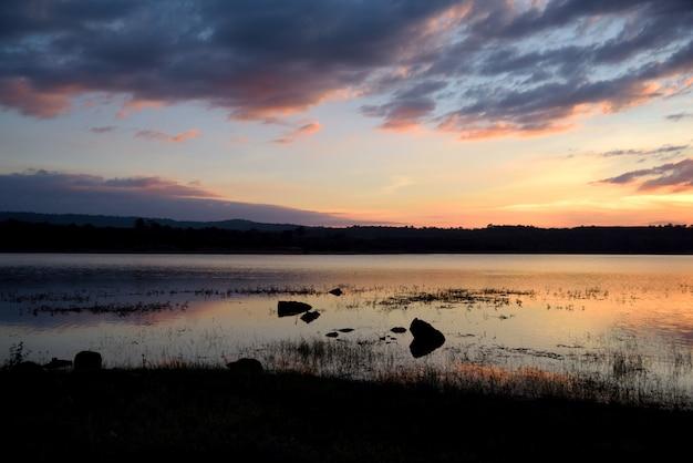 夕日のオレンジ色の背景に川と山の風景