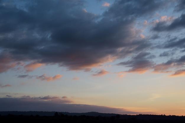 青とオレンジ色の雲空を背景に夕日の山
