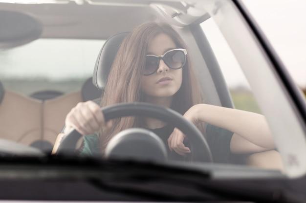車を運転する若い美しい女性