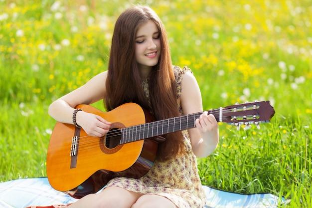 Молодая женщина играет на гитаре