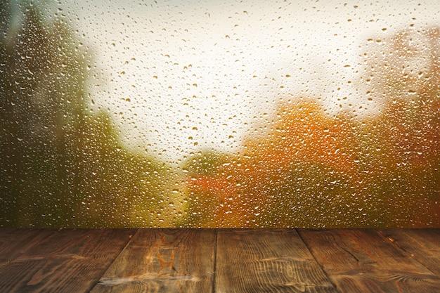 雨のウィンドウの背景上のテーブル