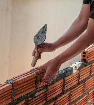 Работник каменщика устанавливая кирпичную кладку на внешнюю стену.