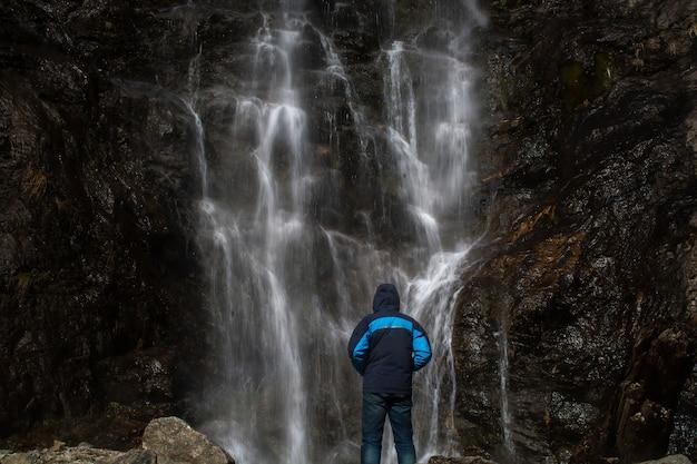 自然を楽しむ旅行者の滝の前に立っている男