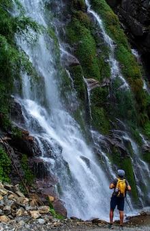 滝、旅行写真を見て立っている男