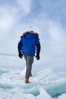 バイカル湖、ロシアの壊れた氷の上を歩く男