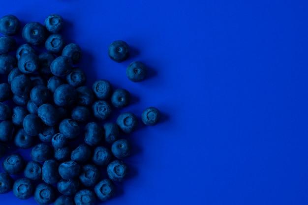 青い紙の背景にブルーベリー、濃いブルーの色調の画像