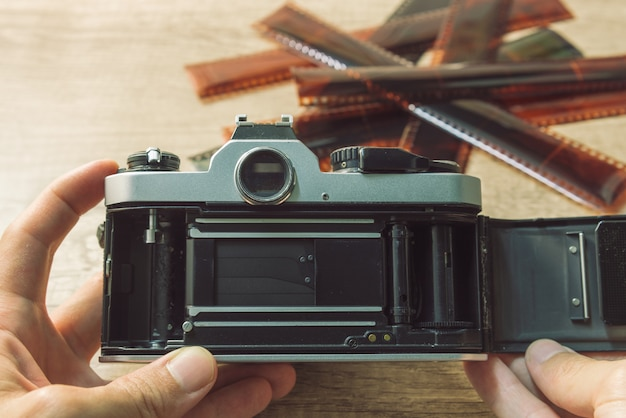ぼやけたフィルムストリップと手でビンテージカメラ。