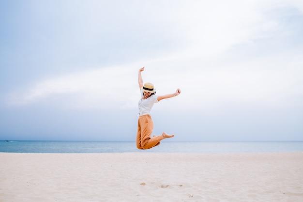 Молодая женщина прыгает на пляже на летние каникулы